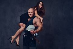 Firefighter holds a woman. Brutal firefighter holds and hot brunette female on his shoulder royalty free stock images