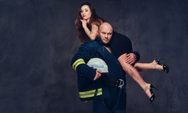 Firefighter holds a woman. Brutal firefighter holds sexy and hot brunette female on his shoulder Stock Image