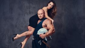 Firefighter holds a woman. Brutal firefighter holds and hot brunette female on his shoulder royalty free stock photo