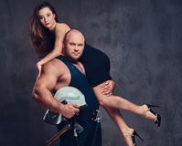 Firefighter holds a woman. Brutal firefighter holds and hot brunette female on his shoulder stock photo