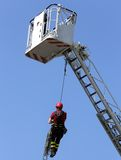 Firefighter hung the rope climbing during the practical exercise. In firehouse stock photos