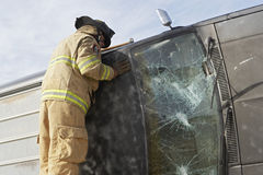 Firefighter Inspecting A Crashed Car Royalty Free Stock Photography