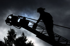 Firefighter on ladder. Firefighter silhouetted on aerial ladder Stock Photo