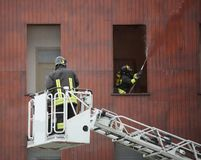 Firefighter on a ladder to reach the top floors of a burning bui Stock Photos