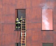 Firefighter with a long ladder while entering the building on fi Stock Photos