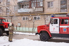 Firefighter looking at an apartment building, near a fire service, there are two machines Royalty Free Stock Photos