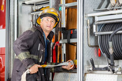 Firefighter Looking Away While Adjusting Hose In Stock Photography