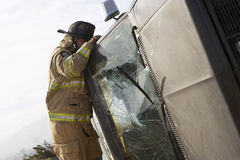 Firefighter Looking Into Crashed Car. Side view of a firefighter inspecting a crashed car Stock Photography