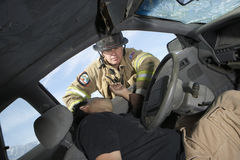 Firefighter Looking Into Crashed Car. Firefighter rescuing car accident victim Royalty Free Stock Photos