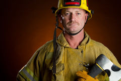 Firefighter Man. Firefighter fireman man holding axe Stock Images