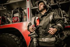 Firefighter near truck. With equipment with water water hose over shoulder Stock Photos