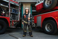 Firefighter near truck. With equipment with water water hose over shoulder Royalty Free Stock Photography
