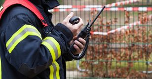 Firefighter operate with a walkie talkie in action - Serie Firefighter Royalty Free Stock Photo