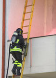 Firefighter with oxygen cylinder climbing a wooden ladder Royalty Free Stock Photo