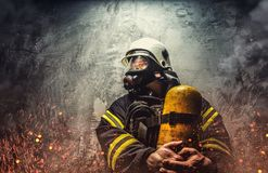 Firefighter in oxygen mask. Firefighter in oxygen mask holds yellow oxygen tank Stock Photography