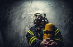 Firefighter in oxygen mask. Firefighter in oxygen mask holds yellow oxygen tank Royalty Free Stock Photography