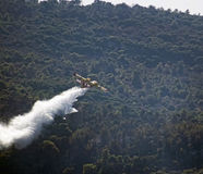 Firefighter plane dropping water over a fire Royalty Free Stock Image