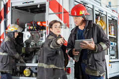 Firefighter Pointing While Colleague Holding. Female firefighter pointing while colleague holding digital tablet against truck at fire station stock photos