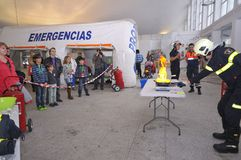 Firefighter. POLA DE SIERO, SPAIN - MAY 2: Firefighter teaching children as a pan is on fire off the April 2, 2015 in Pola de Siero, Spain Stock Photos