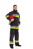 Firefighter posing with helmet under his arm Stock Images