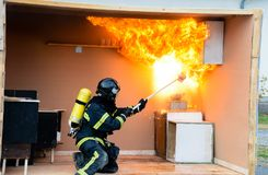 Firefighter pouring water on an oil fire - explosion. Fireman in pouring a water in a kitchen on an oil fire and than explosion followed Royalty Free Stock Photo