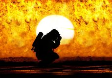 A Firefighter prayer. A firefighter is praying in front of a wild fire in a silhouette Stock Image