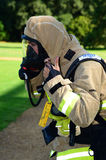 Firefighter prepares his breathing apparatus at fire scene Royalty Free Stock Photography