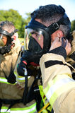 Firefighter prepares his breathing apparatus mask at fire scene Stock Photography