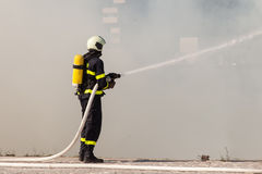 Firefighter in protective suit works with water hose. Fighting for a fire attack Royalty Free Stock Images