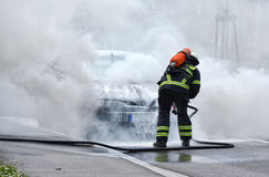 Firefighter is putting out a burning car Stock Photos