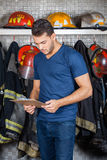 Firefighter Reading Clipboard At Fire Station Royalty Free Stock Photos