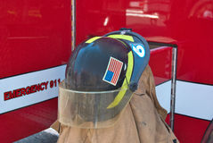 Firefighter's helmet on coat. Fireman's helmet on a coat by red fire truck Royalty Free Stock Image