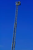 Firefighter's ladder. Lifted up to the blue sky Royalty Free Stock Image