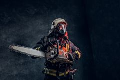 Portrait of a firefighter in safety helmet and oxygen mask holding a chainsaw. Studio photo against a dark textured wall. Firefighter in safety helmet and oxygen royalty free stock photography