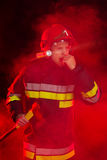 Firefighter shouting in red smoke. Royalty Free Stock Photography