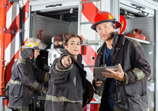 Firefighter Showing Something To Colleague At Fire. Female firefighter showing something to colleague holding digital tablet against truck at fire station Stock Images