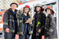 Firefighter Showing Something To Colleagues Royalty Free Stock Images