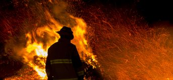 Firefighter silhouette. Firefighter watches a controlled burn at night royalty free stock photo