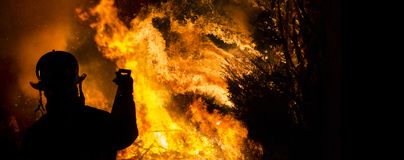 Firefighter silhouette. Firefighter watches a controlled burn at night royalty free stock images