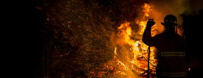 Firefighter silhouette. Firefighter watches a controlled burn at night stock photo