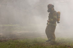 Firefighter in Smoke. A single firefighter standing at a smoky residential fire Stock Image