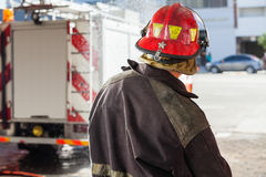 Firefighter Spraying Water At Fire Station Stock Images