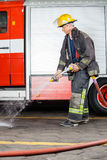 Firefighter Spraying Water On Floor During Royalty Free Stock Photos