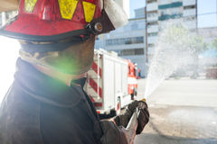 Firefighter Spraying Water While Practicing At Royalty Free Stock Photography