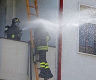 Firefighter sprays water with the spear fighting Stock Photos