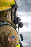 Firefighter Standing By. Soot covered firefighter with flames reflecting in face mask Stock Photo