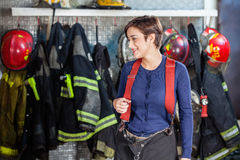 Firefighter Standing Against Uniforms At Fire. Smiling female firefighter standing against uniforms hanging at fire station Royalty Free Stock Photos