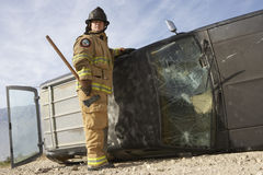 Firefighter Standing By Crashed Car Stock Images