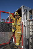 Firefighter Standing At The Fire Brigade's Door. Mature male firefighter standing at the fire brigade's door Royalty Free Stock Images