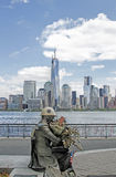 Firefighter Statue Overlooks Freedom Tower. Statue of 911 Fireman on the River Walk in Jersey City, NJ overlooks the new Freedom Tower in New York City Royalty Free Stock Photos